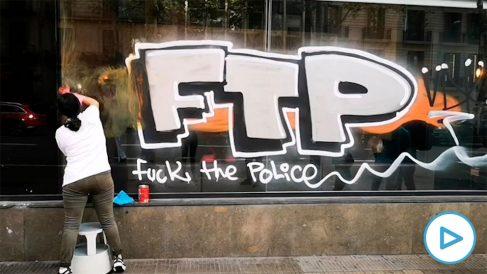 Una mujer limpia una pintada contra la Policía en un escaparate del centro de Barcelona.