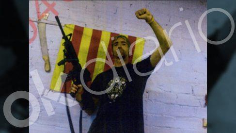 Alexis Codina, uno de los CDR, posando con un arma y una bandera.