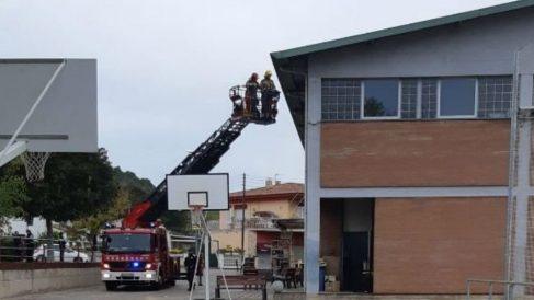 Los bomberos retiran lazos amarillos de la fachada de un colegio electoral en Sarrià de Sarrià (Gerona). (Ep)