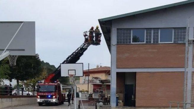 Los bomberos retiran lazos amarillos de la fachada de un colegio en Gerona