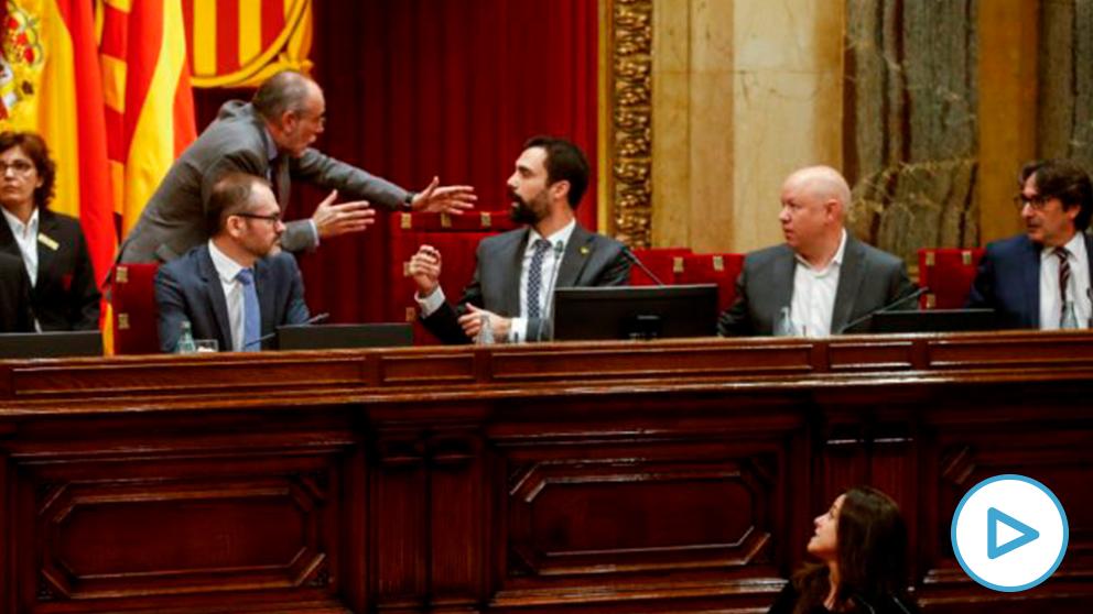 La diputada de la CUP en el Parlament de Cataluña, Maria Sirvent (abajo), interviene este martes ante el pleno, mientras el presidente de la cámara catalana, Roger Torrent (c), discute con el letrado mayor, Joan Ridao (2i). La sesión plenaria del Parlament vota una moción de la CUP que habla de autodeterminación, un texto cuya admisión a trámite ha recurrido el Gobierno central ante el TC, que ya ha advertido en varias ocasiones de las posibles consecuencias penales en casos de este tipo. EFE/Quique García