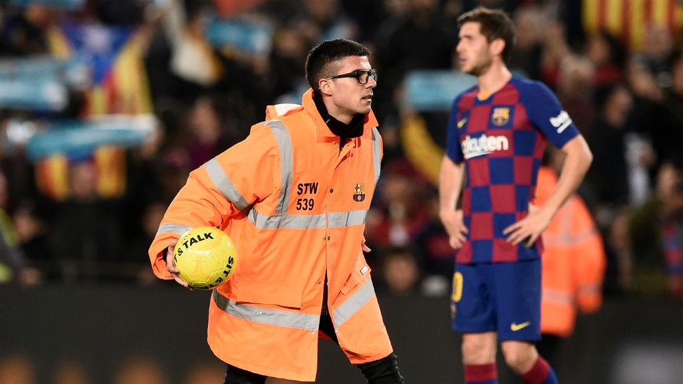 Un miembro de seguridad retira uno de los balones amarillos lanzados al campo durante el Clásico. (AFP)