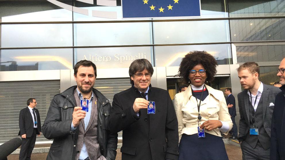 Toni Comín, Carles Puigdemont y la eurodiputada nacionalista flamenca Assita Kanko enseñan sus acreditaciones de eurodiputados.