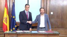 Pedro Sánchez, presidente del Gobierno en funciones, con Pablo Iglesias, secretario general de Podemos, firmando su pacto de Gobierno en el Congreso de los Diputados.
