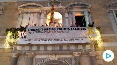 Miembros de la ANC colocan la pancarta de los presos en el balcón de la Generalitat.
