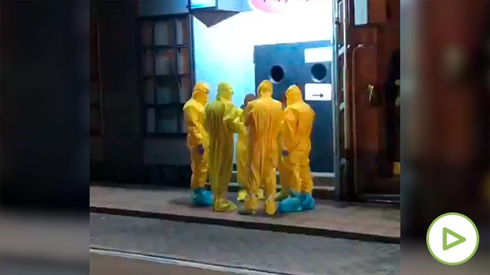 Técnicos sanitarios con trajes de aislamiento a la puerta del pub donde se encontraba la mujer a la que se ha analizado por sospechas de coronavirus.