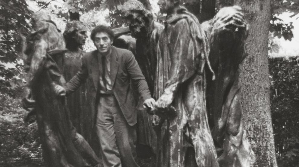 Alberto Giacometti en el parque de Eugène Rudier en Vésinet, posando junto a Les Bourgeois de Calais «Burgueses de Calais» de Rodin, 1950 @PatriciaMatisse @Fondation Giacometti