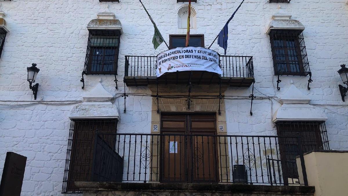 Pancartas en la fachada del ayuntamiento de Montefrío anunciando el cierre de las instalaciones y con las banderas a media asta por el campo español.