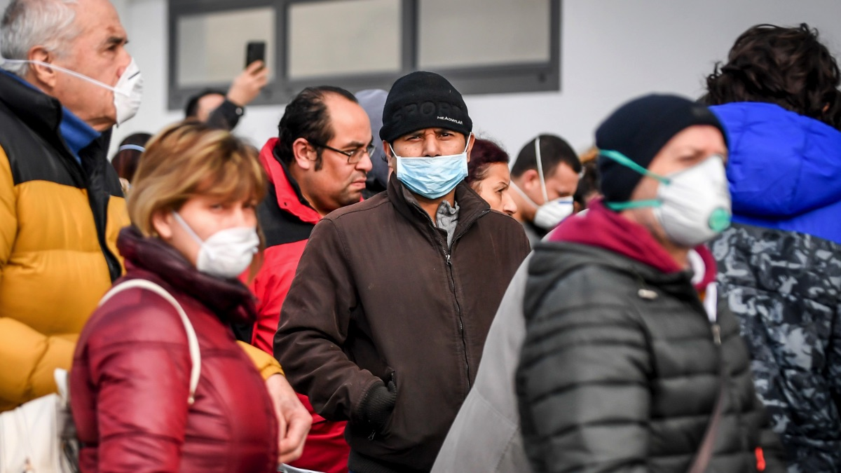 Italianos con máscaras en frente de un supermercado esperando para comprar reservas en plena crisis del coronavirus. (Foto. EP)