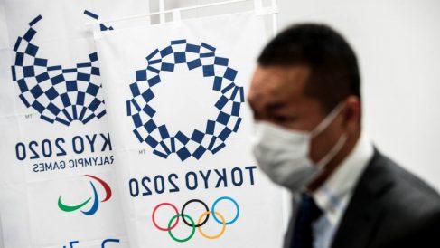 Un reportero con mascarilla ante un stand de los Juegos de Tokio 2020. (AFP)