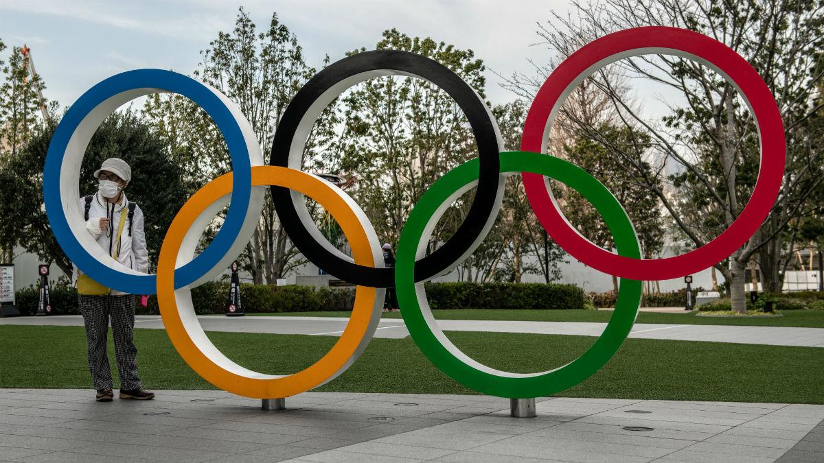 Una persona con mascarilla posa con los anillos olímpicos. (Getty)