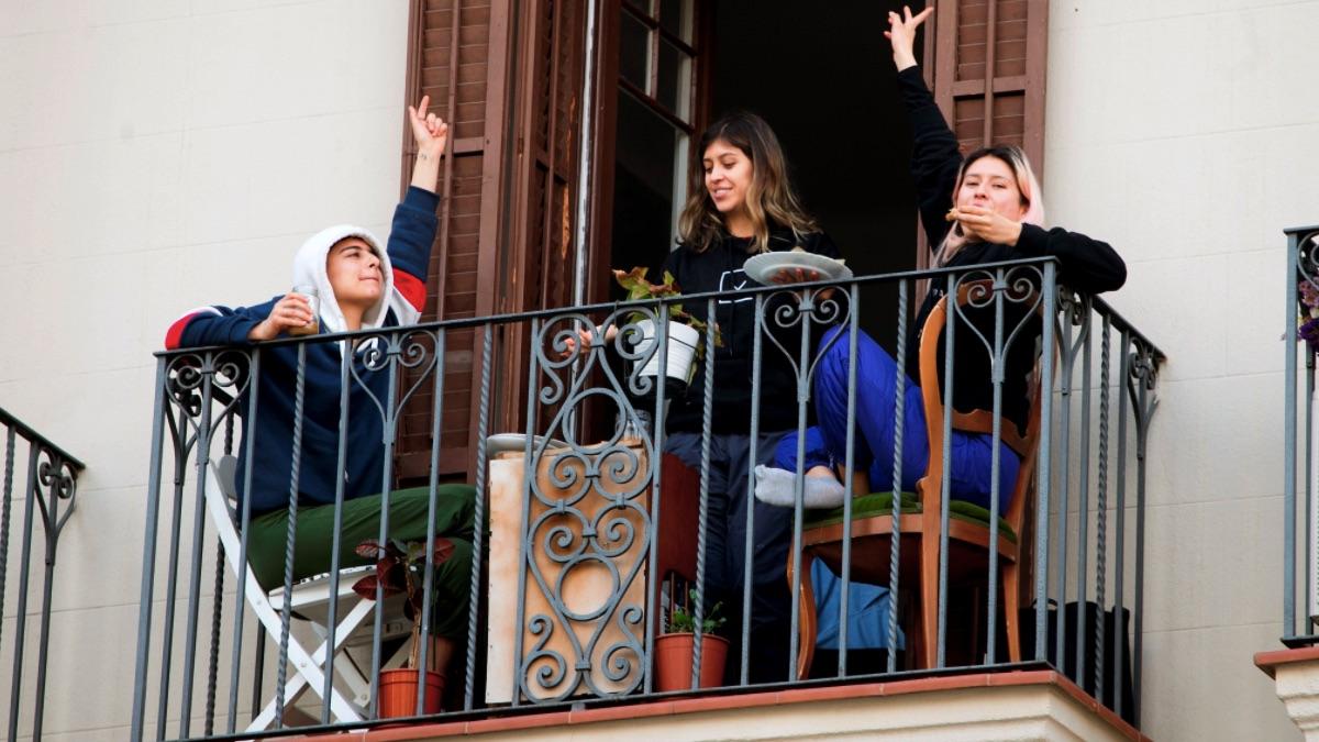 Vecinos comiendo en el balcón durante la crisis por el coronavirus. (Foto: EFE)