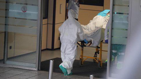 Un profesional sanitario llevando a un enfermo en camilla (Foto: EP)