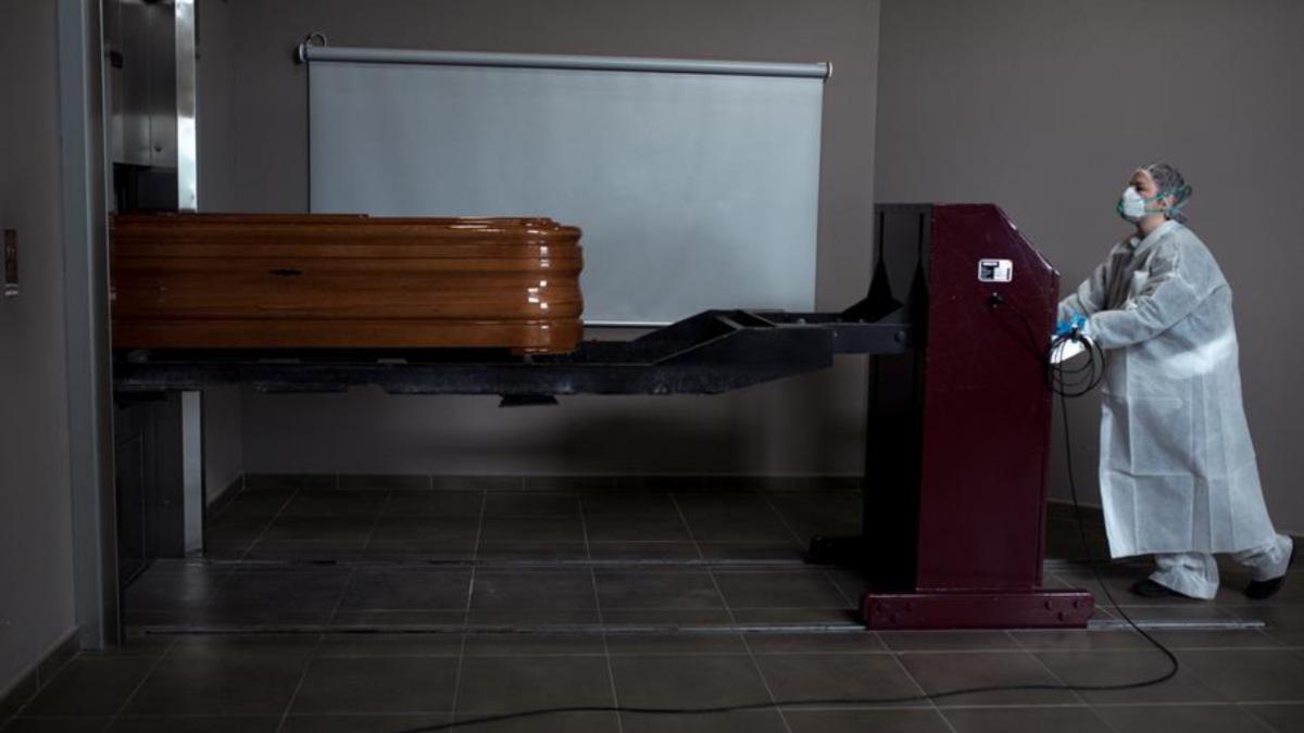 Una operaria de una funeraria transporta el féretro de un fallecido por coronavirus (EFE).