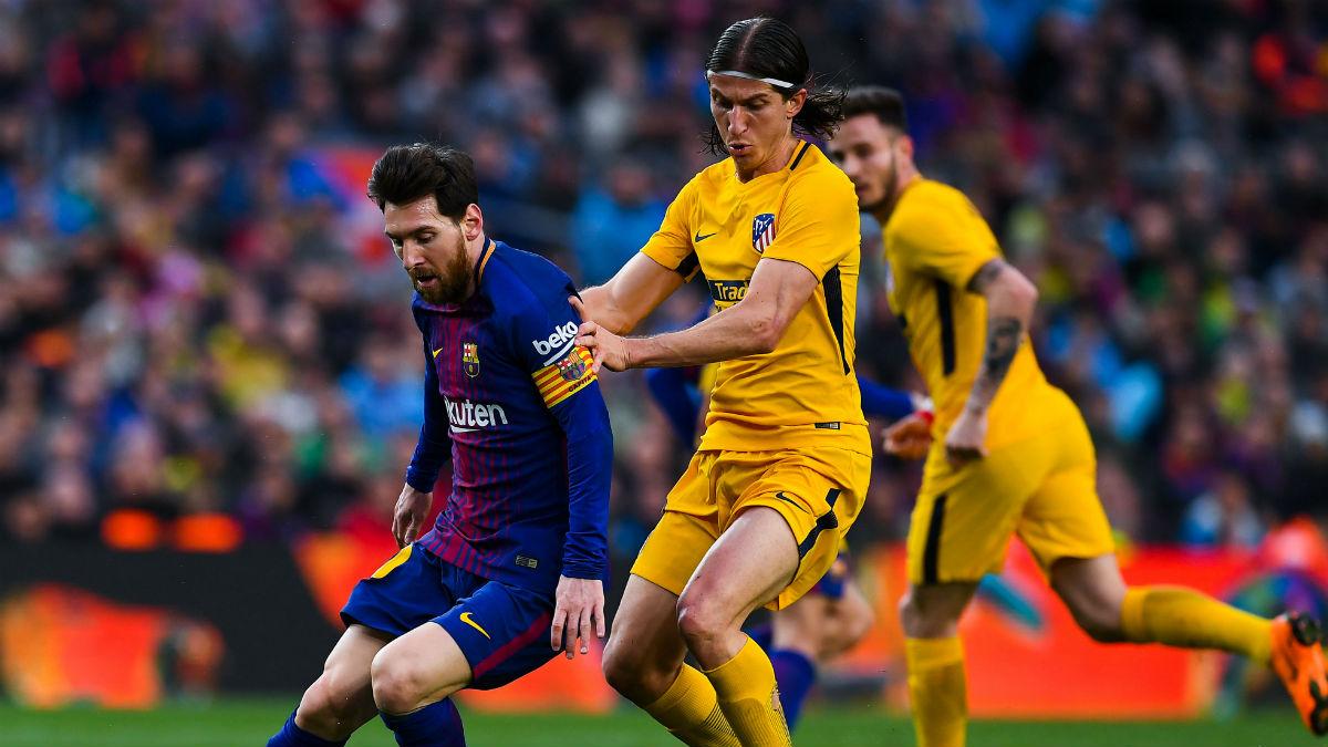 Filipe Luis junto a Messi pugnando por un balón. (Getty)