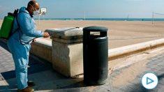 Un operario desinfecta una papelera ante una playa de la Malvarrosa (Valencia) este miércoles. EFE/ Juan Carlos Cárdenas