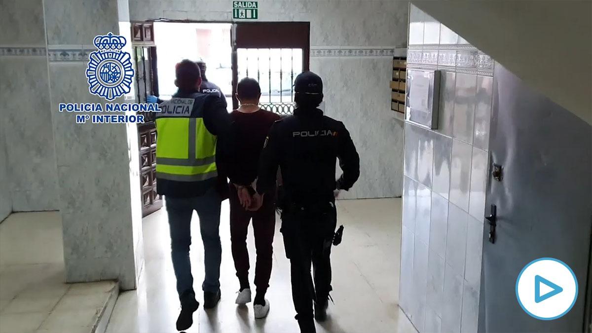 El detenido, custodiado por dos agentes.