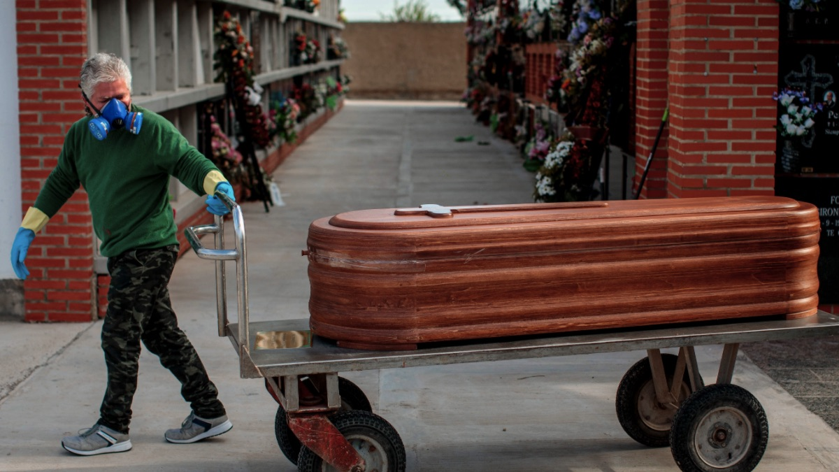 Un operario de un cementerio de València traslada un féretro seguido por los familiares de la víctima durante un entierro. (Foto: EFE:Biel Aliño)