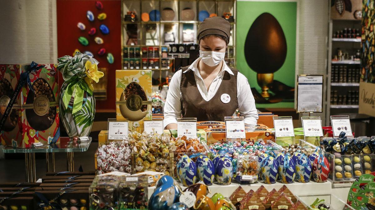Una dependienta con mascarilla atiende en una pastelería de Roma (Foto: Europa Press).