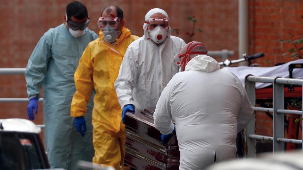 Trabajadores de una funeraria protegidos trasladan de la morgue a un fallecido por coronavirus. (Foto: EFE)