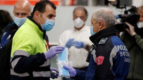 Policías entregan mascarillas en la estación de metro de Nuevos Ministerios en Madrid. Foto: EFE