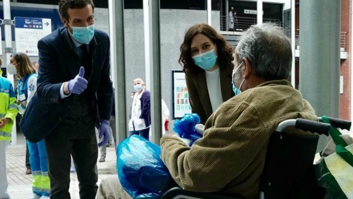 Pablo Casado e Isabel Díaz Ayuso saludan a un paciente en el hospital de canpa d Efema.