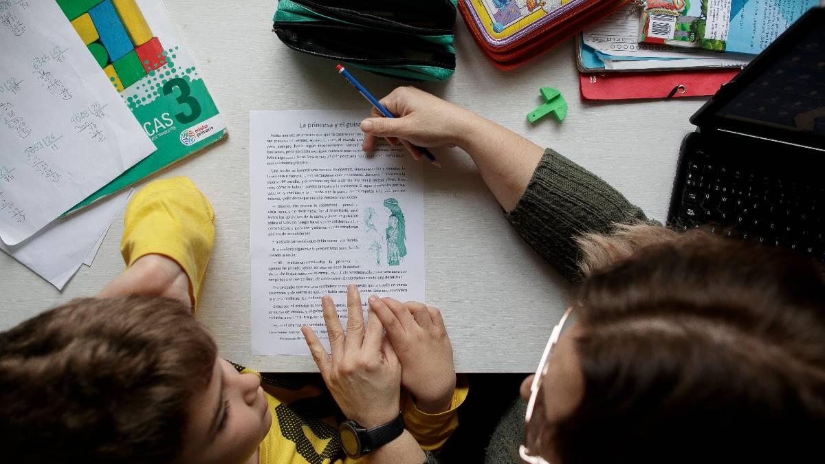 Un niño estudia y hace los deberes en casa con la ayuda de su madre. Foto: EP