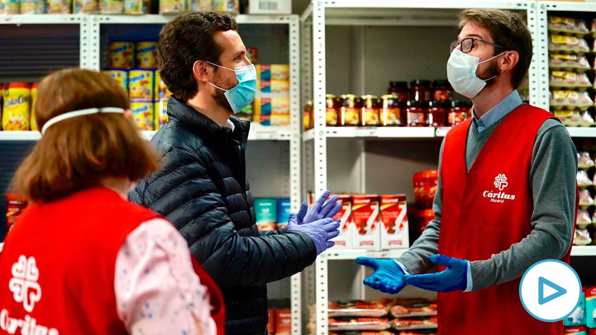 La visita de Pablo Casado  al economato de Cáritas con una mascarilla y unos guantes de látex.