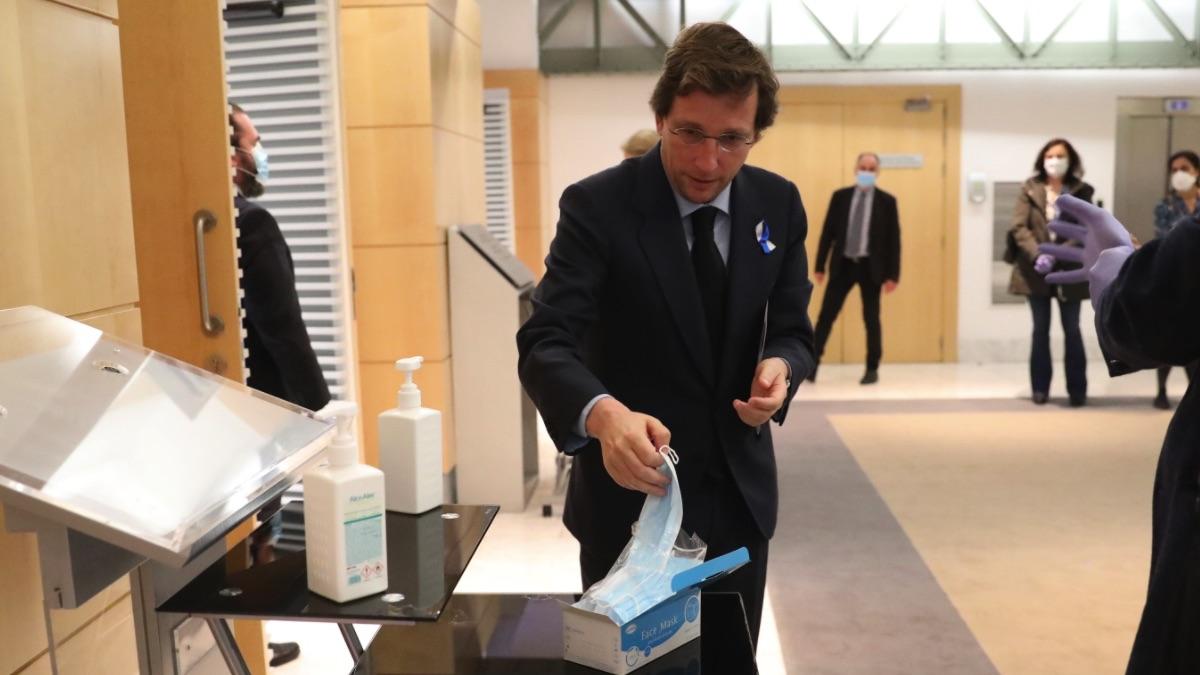 José Luis Martínez-Almeida colocándose una mascarilla antes de un Pleno en Cibeles. (Foto: Madrid)