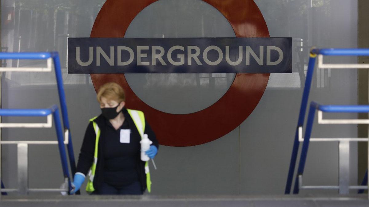 Una limpiadora del metro de Londres desinfecta una barandilla para evitar el contagio de coronavirus. Foto: AFP