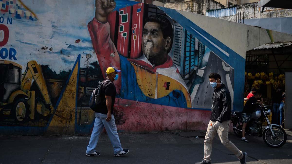 Dos venezolanos llevando mascarillas para protegerse contra el coronavirus por una calle de Caracas, la capital de Venezuela. Foto: AFP