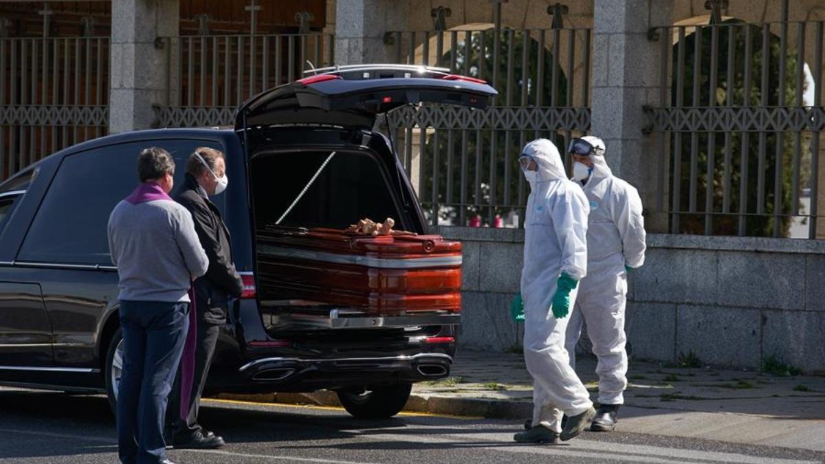 Operarios de una funeraria manejan el ataúd de una víctima del coronavirus.