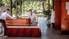 Operarios de una funeraria de Valencia manejan el féretro de una víctima del COVID-19.