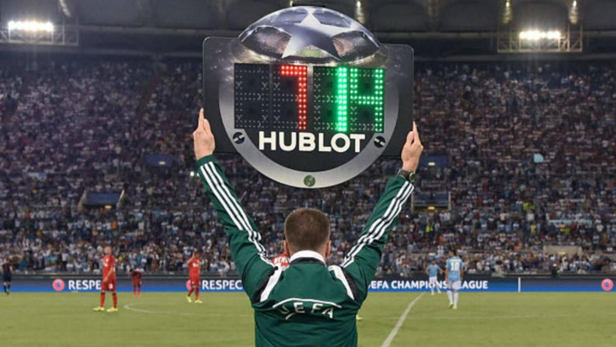 Un árbitro levanta el cartel de cambios durante un partido.