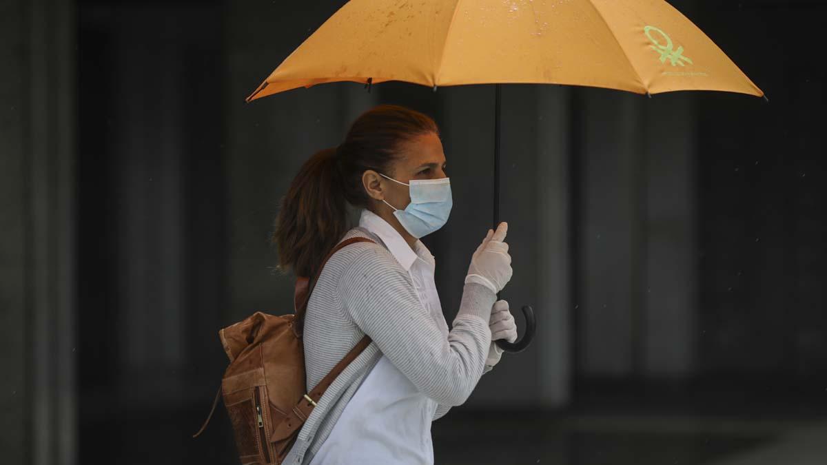 Una mujer con mascarilla camina por la calle resguardada de la lluvia bajo su paraguas. Foto: EP