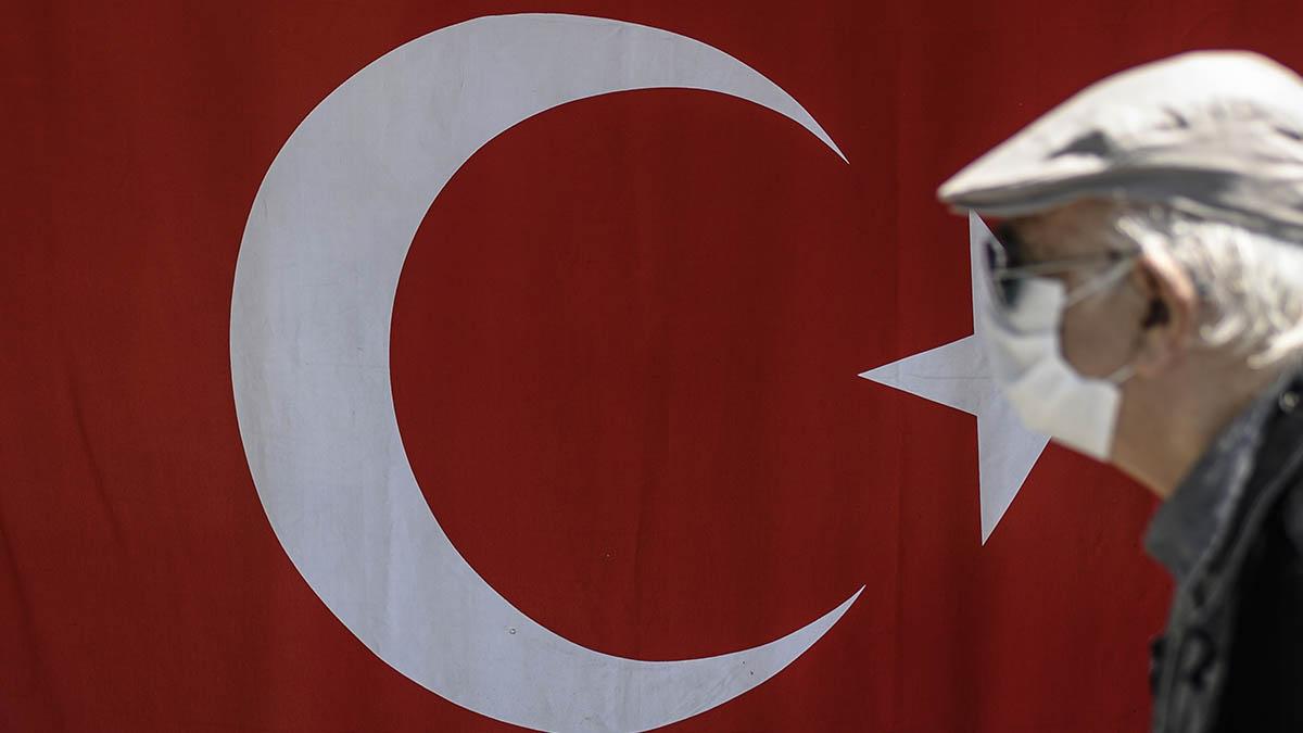 Un ciudadano turco con mascarilla pasa delante de una bandera del país en Estambul. (Afp)