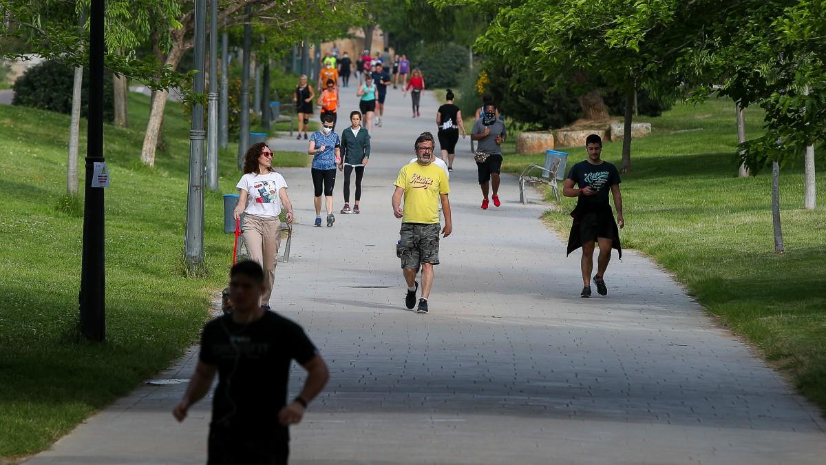 Personas caminan por el parque del Río Turia durante su franja horaria permitida en la desescalada ante la crisis del Covid-19 en la que mayores de 14 años y menores de 69 tienen permitidas las salidas para pasear y hacer deporte – Iván Terrón – (Europa Press)
