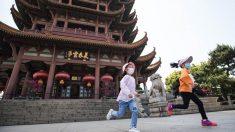 Unos niños con mascarilla juegan en las calles de Wuhan.