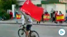 Una persona saca la bandera comunista en las protestas contra Sánchez.