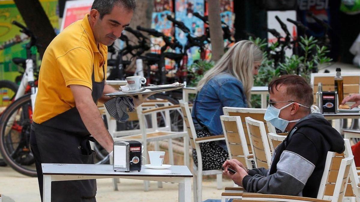 Camarero y cliente en una terraza.