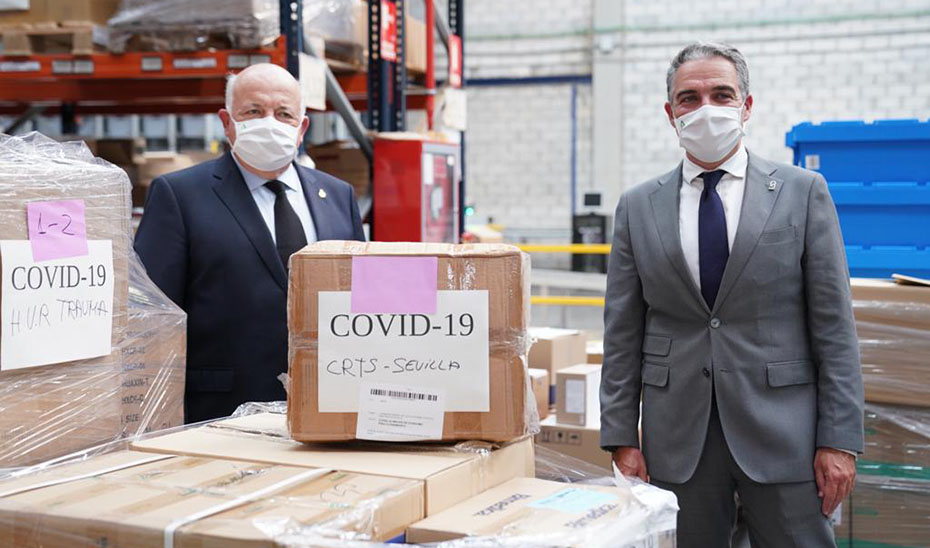 Los consejeros Jesús Aguirre y Elías Bendodo, en el centro logístico del SAS.