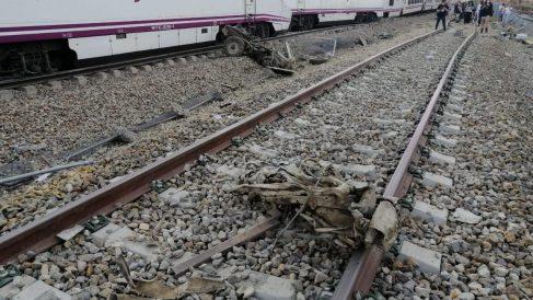 El tren Alvia accidentado con partes del coche en primer término y algunos pasajeros andando por las vías. Foto cedida