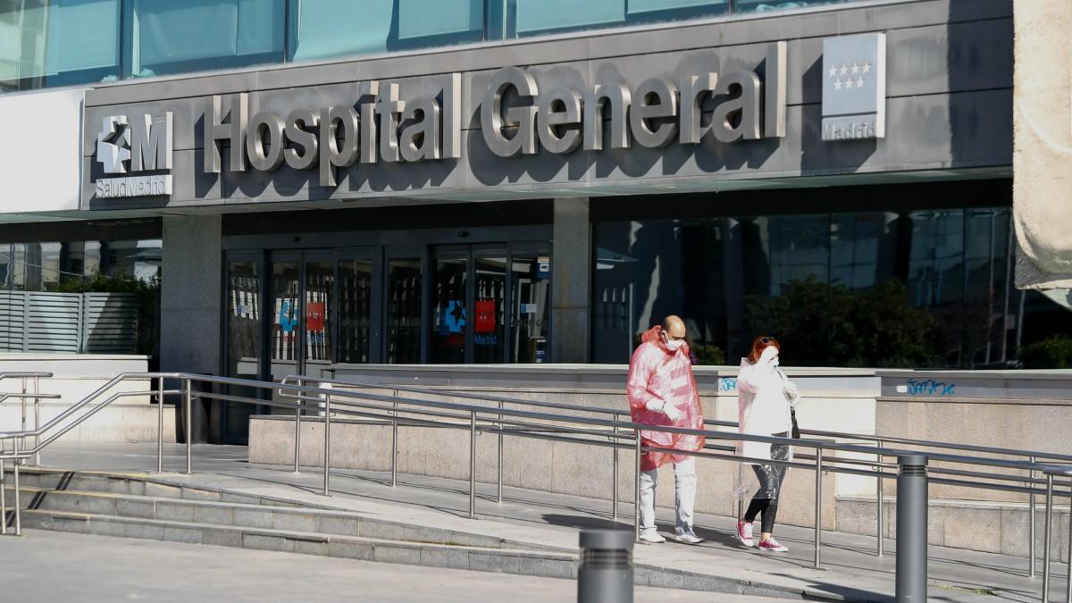 Dos personas protegidas con mascarillas salen del Hospital La Paz. Óscar J.Barroso – Europa Press)