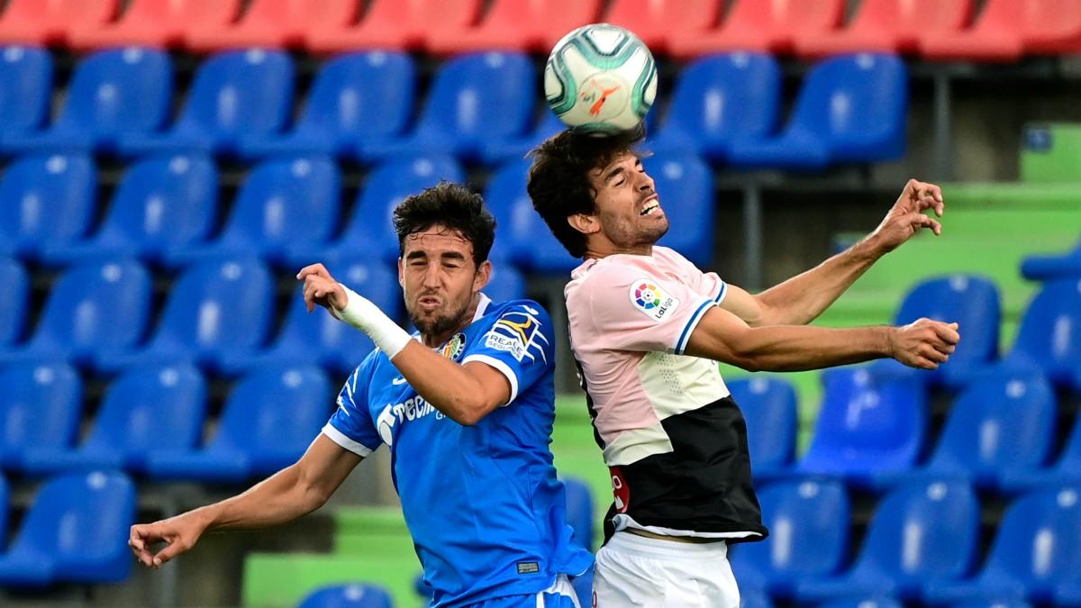 Jaime Mata y Sebastien Corchia saltan a por un balón durante el Getafe – Espanyol. (AFP)