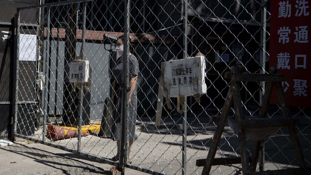 Una mujer espera un pedido online que ha realizado dentro de los límites de uno de los barrios confinados en la capital china por el rebrote de coronavirus en 2020. Foto: AFP
