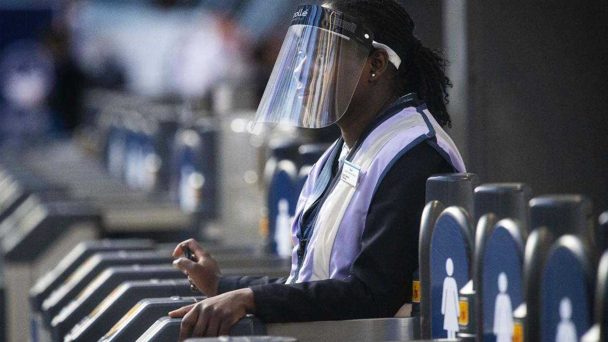 Trabajadora con pantalla protectora en la estación de Waterloo, en Londres (Victoria Jones/PA Wire/dpa)