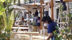 Empleados de un restaurante en Cataluña, preparando las mesas en el exterior.