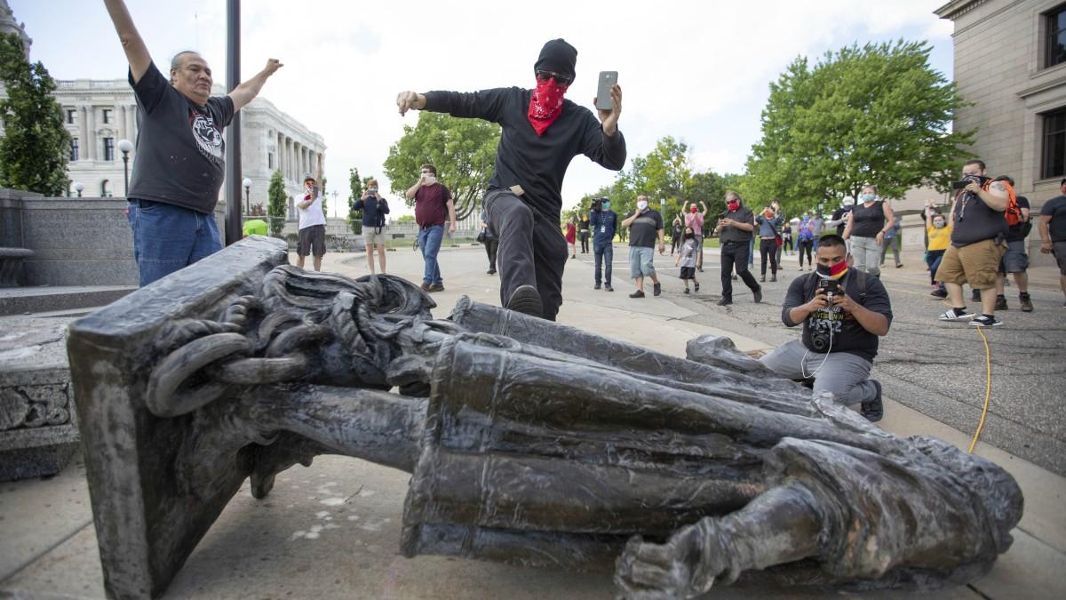 Un hombre patea la estatua de Cristóbal Colón que se encuentra en el suelo después de ser derribado ante el Capitolio del Estado de Minnesota. (Chris Juhn / ZUMA Wire / dpa – Chris Juhn / ZUMA Wire / dpa)