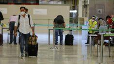 Pasajeros procedentes de Londres rellenan un formulario covid a su llegada a Barajas. (Jesús Hellín / Europa Press)