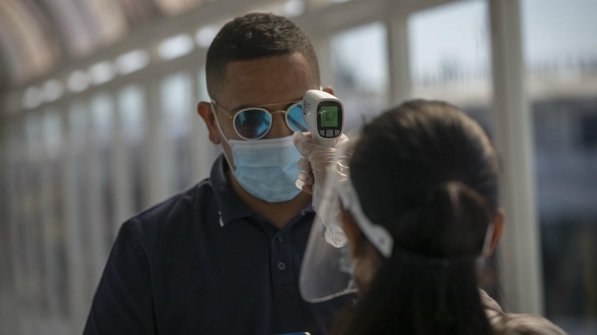 Una trabajadora de la naviera FRS toma la temperatura a un pasajero antes de embarcar durante la reanudación de la ruta Algeciras-Ceuta, en el Puerto de Algeciras. (María José López – Europa Press)